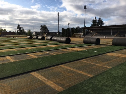 Synthetic turf at Goddard Stadium being rolled up