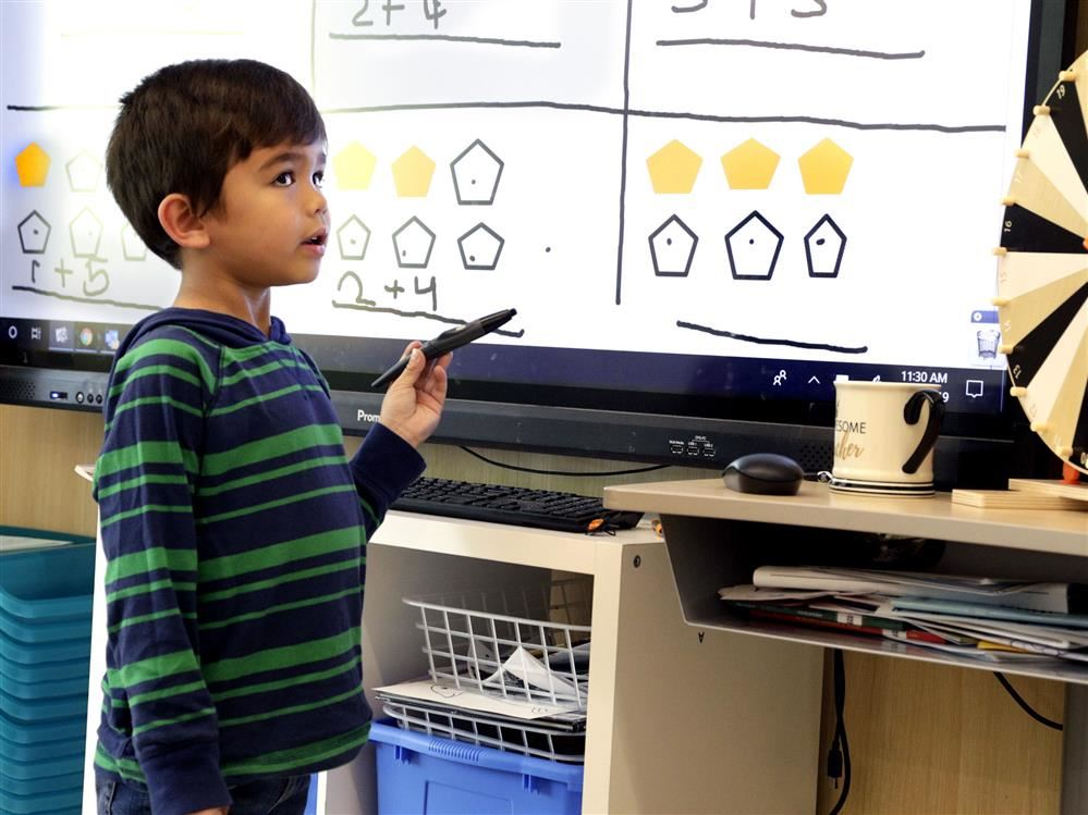 Kindergarten boy doing math on a whiteboard