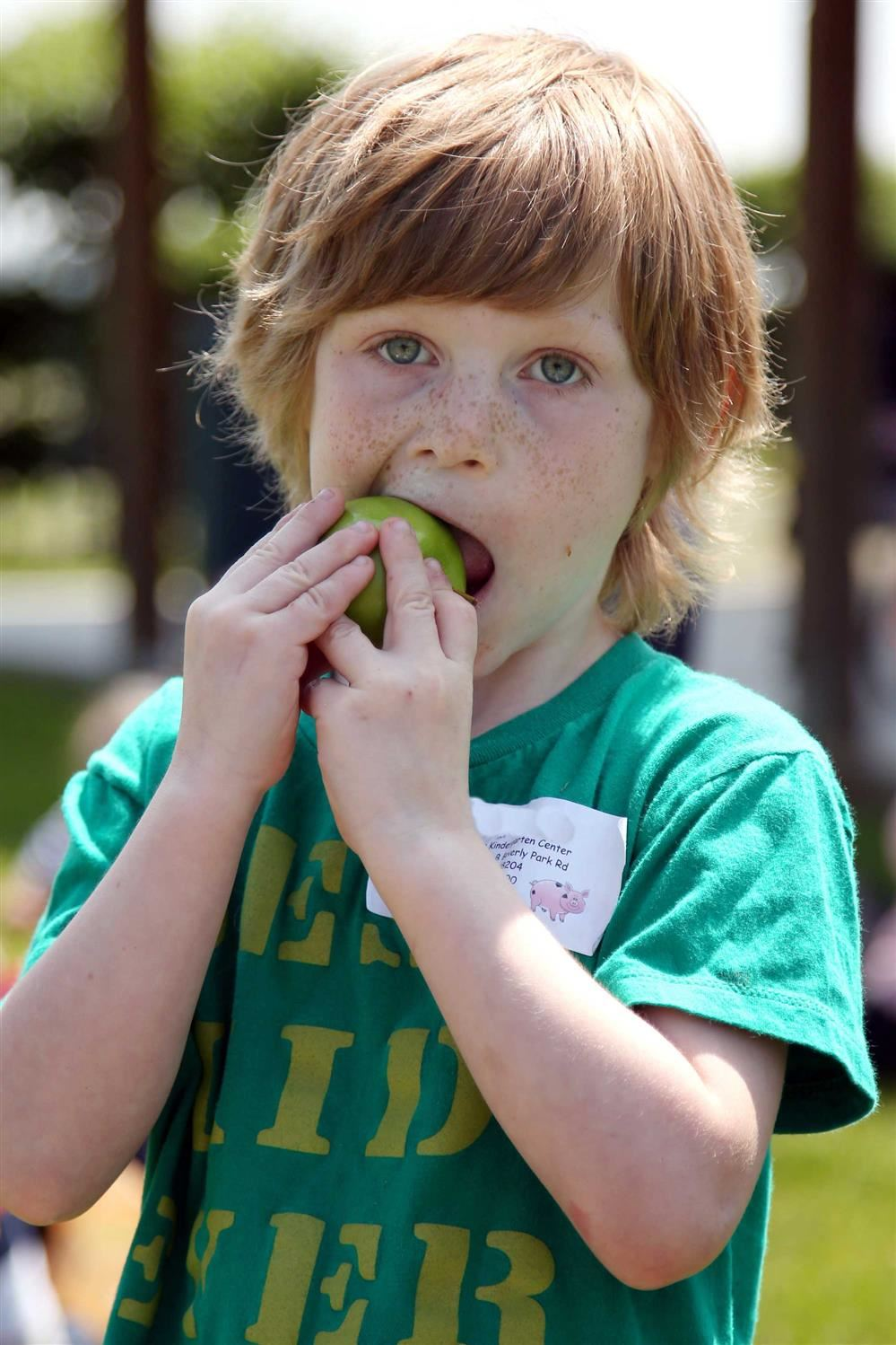 Young red-headed boy eating a green apple