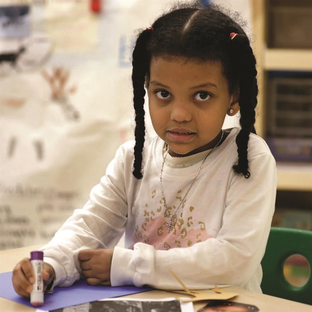 Kindergarten girl of color in classroom