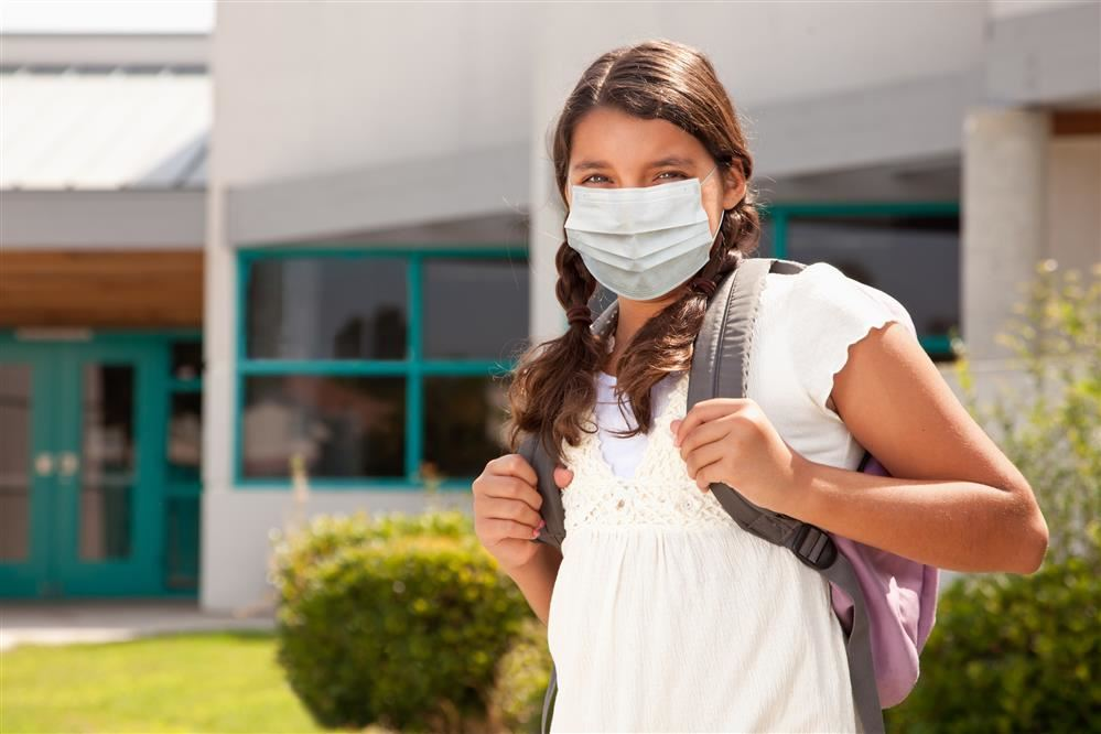elementary girl wearing mask outside a school building